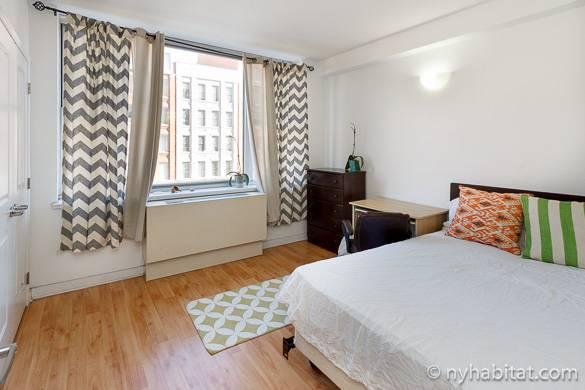 Bild eines hellen Schlafzimmers mit Fenster, Doppelbett und Schreibtisch in NY-16161