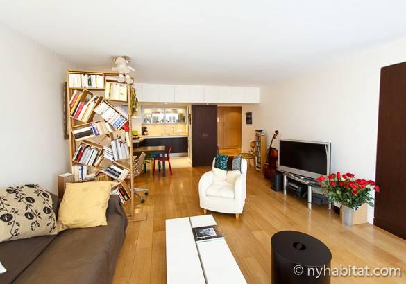 Bild des Wohnzimmers der Wohnung PA-3808 mit einem asymmetrischen Bücherregal und einem Flachbildfernseher.