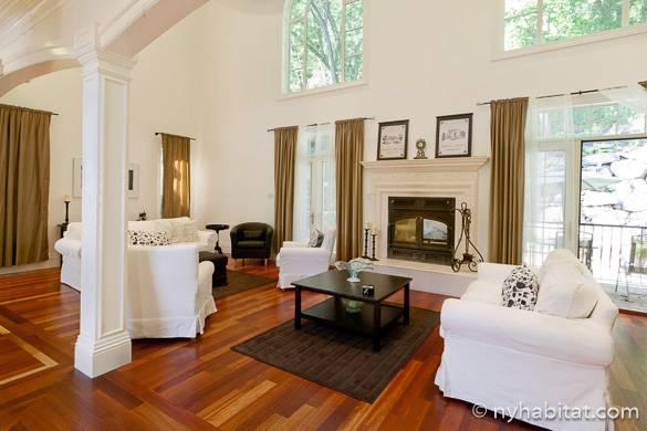 Bild des Wohnzimmers in NY-15040 in Staten Island mit großen Fenstern, die auf den grünen Garten blicken.