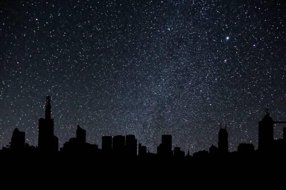 Bild der New Yorker Skyline bei Nacht unter einem Sternenhimmel.
