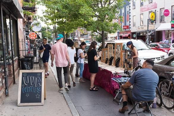 Bild von Straßenhändlern, die auf einem Bürgersteig in NYC Schmuck verkaufen.