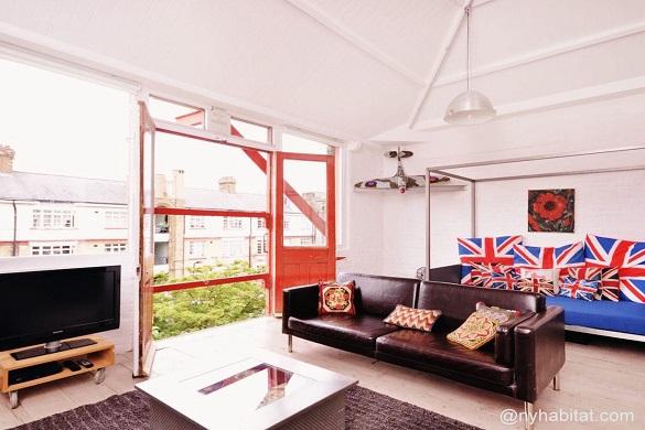 Bild des Wohnzimmers von LN-573 mit Kissen mit der britischen Flagge auf einem Sofa und einem großen offenen Fenster, welches typische englische Gebäude überblickt