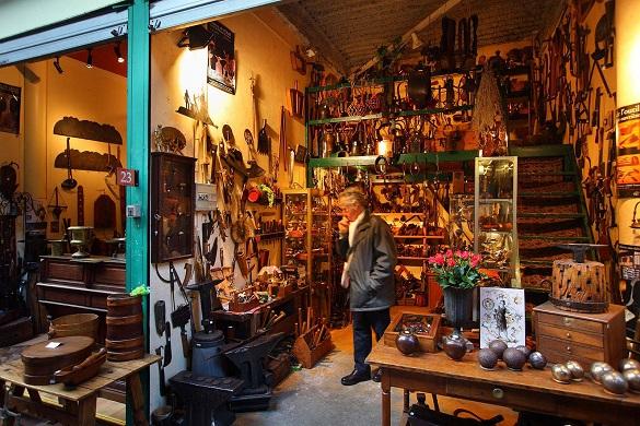 Bild eines Mannes in einem Marktstand, der mit Antiquitäten und Haushaltsartikeln gefüllt ist