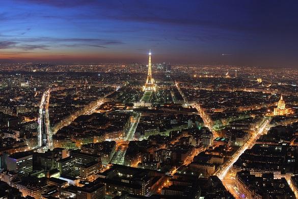 Bild der Pariser Skyline bei Nacht vom Tour Montparnasse mit dem Eiffelturm im Hintergrund