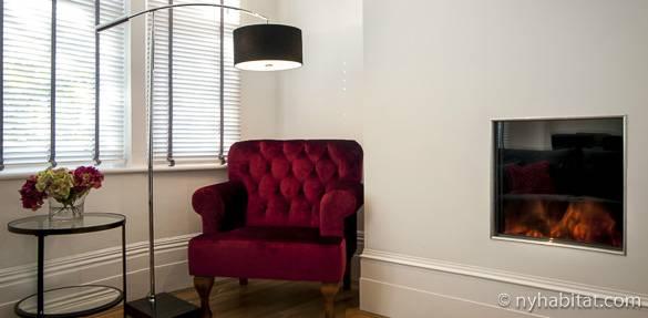Ein farbintensiver Sessel neben einem verglasten Kamin