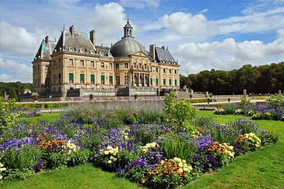 Bild eines barocken französischen Schlosses mit farbenfrohen Gärten