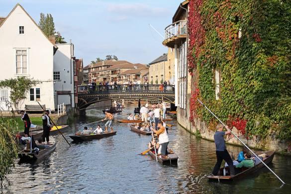 Bild von Touristen, die auf dem River Cam in Cambridge in England eine Ruderbootstour machen
