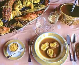 Photographie d'une bouillabaisse servie de manière traditionnelle sur une table à Marseille