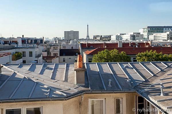 Photo d'une vue sur les toits de Paris et sur la tour Eiffel prise d'un studio T1 à Montparnasse