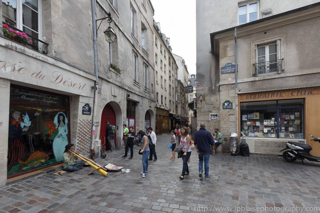 Photo d'un musicien en train de jouer pour des touristes dans une rue pavée du Marais, à Paris