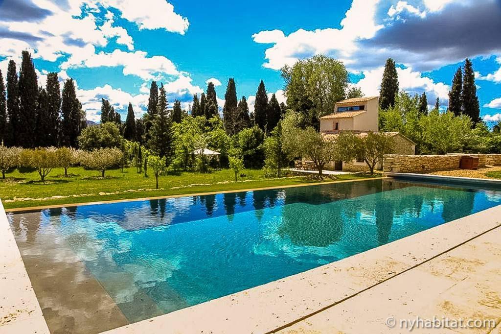 Photo d'une piscine à débordement derrière laquelle on peut voir le jardin et la dépendance du mas provençal