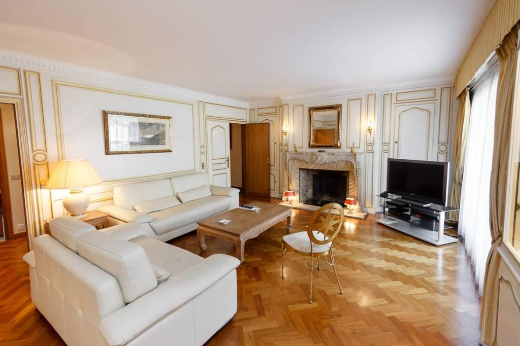 Photo du salon d'un appartement, situé dans le quartier du Trocadéro, pourvu d'une cheminée et de parquet
