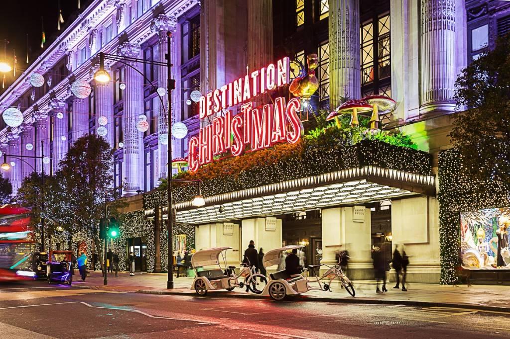 Photo d'un bâtiment, entouré de massifs et de sapins, sur Oxford Street orné d'illuminations de Noël et d'un grand écriteau rouge sur lequel on peut lire « DESTINATION CHRISTMAS »