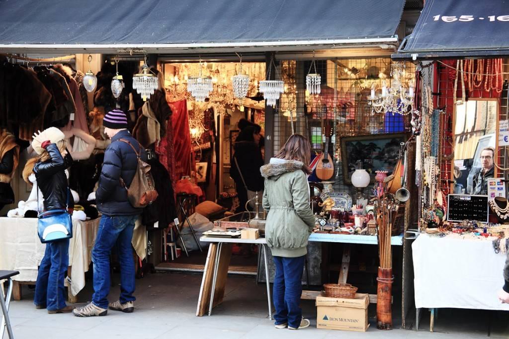 Photo de visiteurs jetant un œil aux étals d'antiquités du marché de Portobello Road. Plusieurs objets sont exposés autour d'eux
