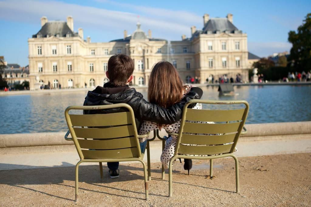 Photo d'un couple blotti l'un contre l'autre, lisant devant le Palais du Luxembourg à Paris