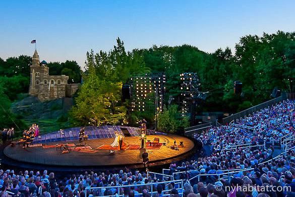 Photo de spectateurs assistant à une représentation en plein air d'une pièce de Shakespeare avec, en arrière-plan, un château