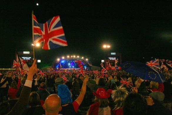 Photographie de la foule qui assiste au concert en plein air en agitant des drapeaux britanniques