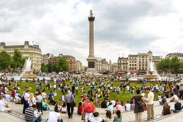 Photographie de personnes assises dans l'herbe avec des fontaines et une statue