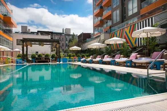 Photographie de la piscine extérieure du McCarren Hotel avec des tables à côté équipées de parasols
