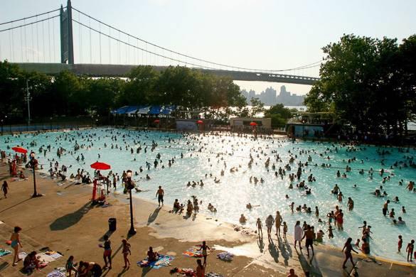 Photographie de personnes en train de se baigner dans la piscine d'Astoria Park avec le Triboro Bridge en arrière-plan