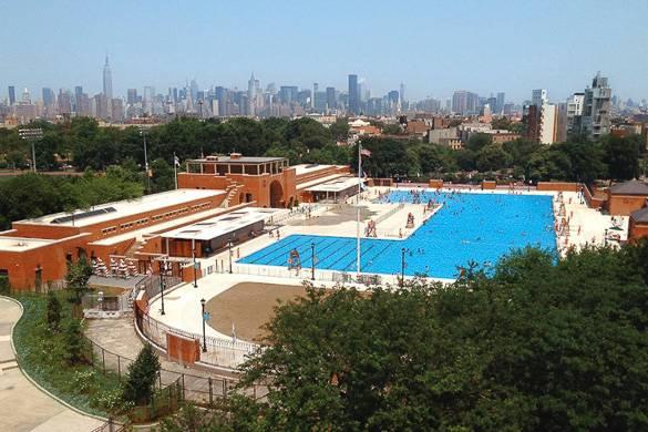 Photographie de la piscine publique de McCarren Park avec la skyline de Manhattan au loin