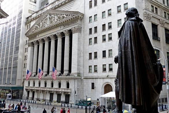 Photo de la bourse de Wall Street avec le drapeau américain et la statue en premier plan