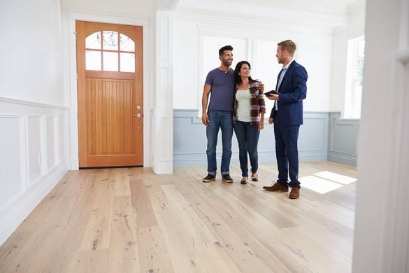 Photo d'un agent immobilier en conversation avec des clients à l'intérieur d'un logement