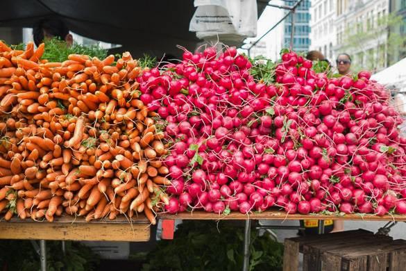 Photo de carottes et de radis sur le stand d'un marché fermier de la ville