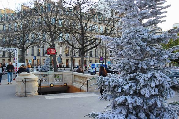 Photo d'un sapin de Noël près d'une bouche du métro parisien