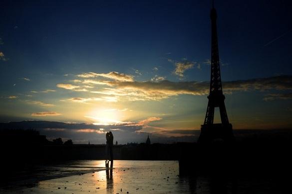 Photo d'un couple au coucher du soleil avec la tour Eiffel en arrière-plan.