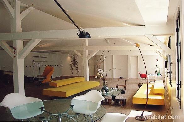 Photo de la grande pièce à vivre du PA-1516 aux murs blancs et des canapés aux coussins jaunes