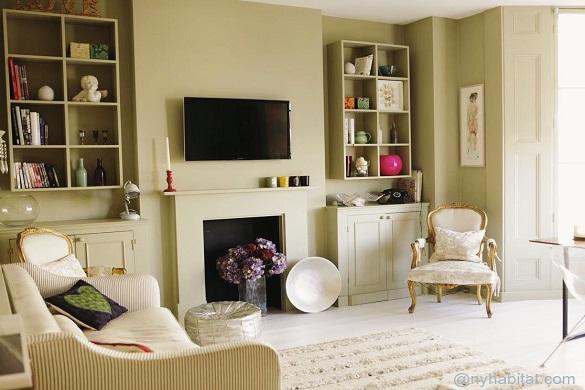 Photo du salon du LN-1185 avec cheminée décorative, canapé et fauteuil