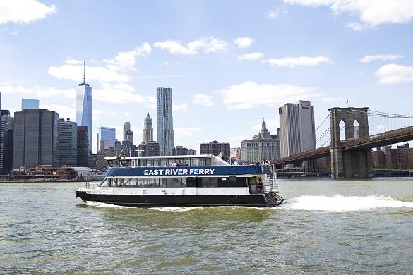 Photo de l'East River Ferry passant près du Brooklyn Bridge et de la skyline de Manhattan en arrière-plan
