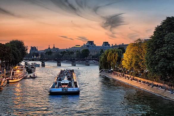 Photo d'un bateau parisien sur la Seine au crépuscule