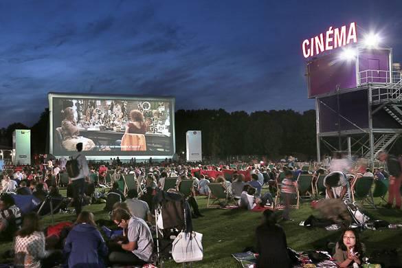 Photo de personne assises dans l'herbe regardant un film en plein air