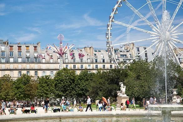 Photo de la Fête des Tuileries avec une grande roue, des manèges et des fontaines