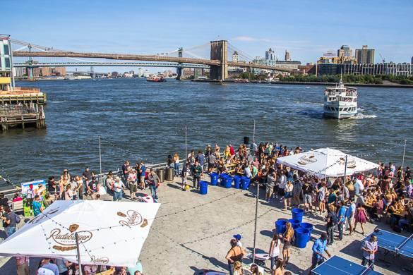 Photo d'un festival en plein air au bord de l'eau avec le pont de Brooklyn et un ferry en arrière-plan