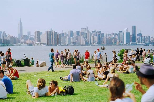 Photo de gens assis sur l'herbe à l'East River State Park avec la skyline de Manhattan en arrière-plan