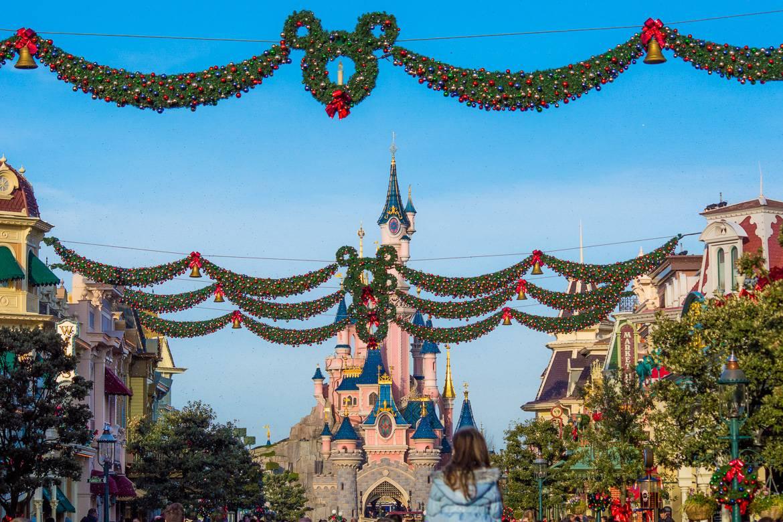 Photo du Château de Cendrillon à Disneyland Paris avec des couronnes de Noël en forme de Mickey Mouse bordant la rue