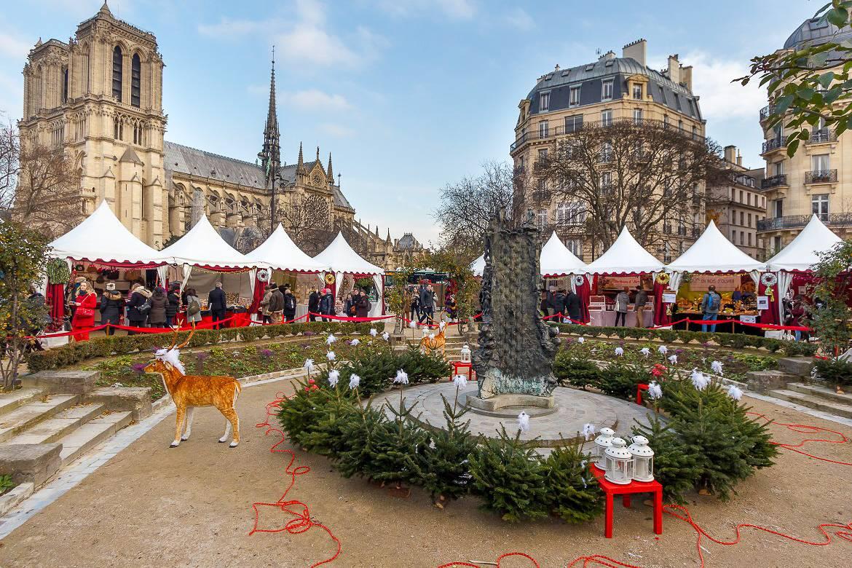 Photo d'étals de marché de Noël avec un renne et la cathédrale Notre-Dame de Paris en arrière-plan