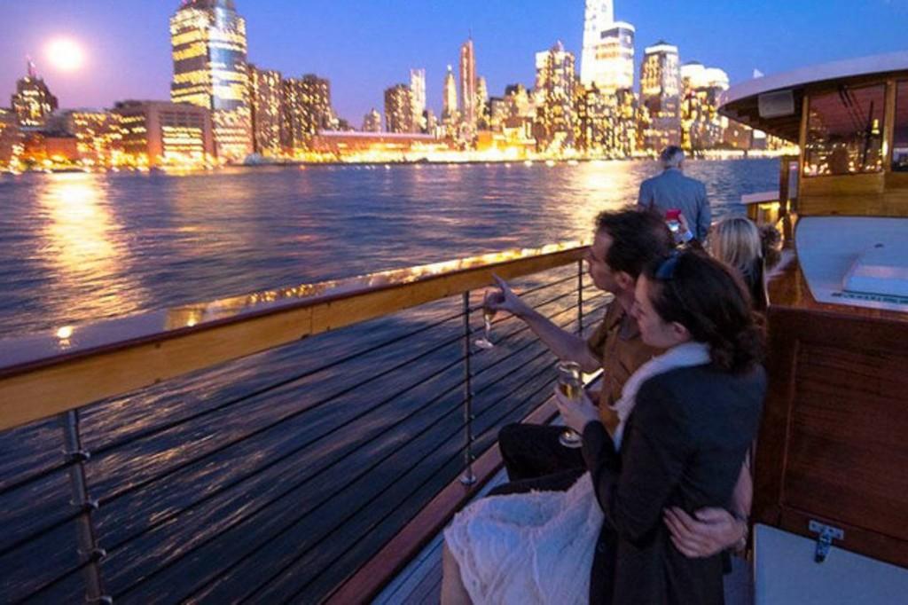 Photo de personnes en croisière sur un yacht avec la skyline new-yorkaise en arrière-plan