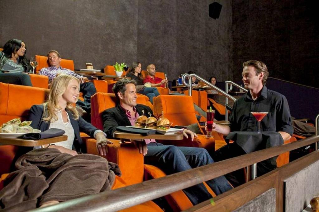 Photo de personnes au cinéma en train de dîner en regardant un film et d'un serveur leur apportant des cocktails