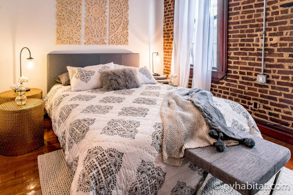 Photo de la chambre de l'appartement NY-17254 dans le West Village dotée de murs en brique apparente et d'un lit confortable
