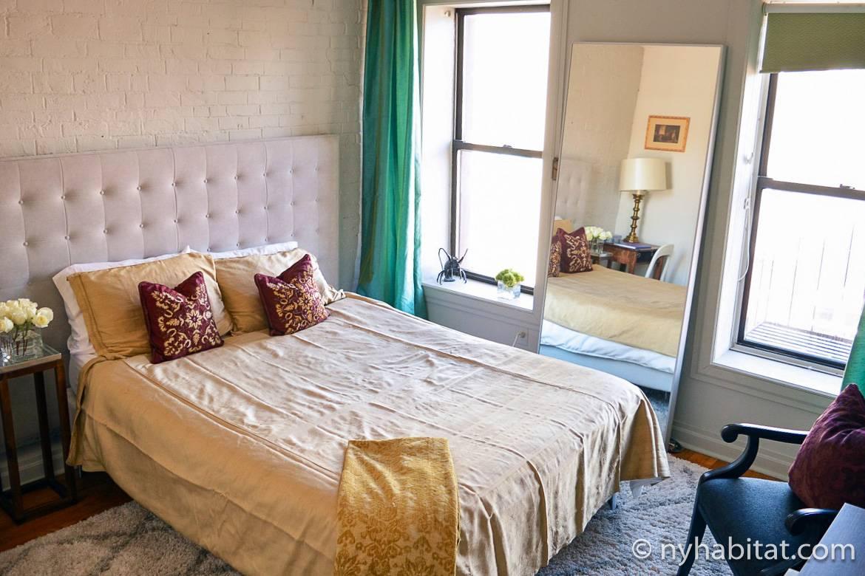 Photo du lit à ossature en bois avec coussins décoratifs dans la chambre de l'appartement NY-11476 dans l'East Village
