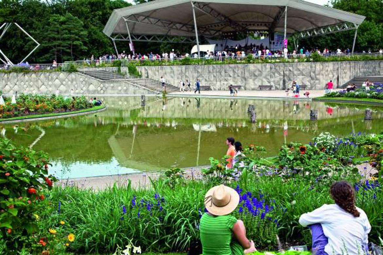 Photo de personnes assises parmi les plantes et les fleurs d'un parc à Paris