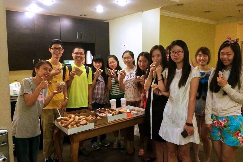 Photo d'un groupe de résidents rassemblés dans une des cuisines communes de la résidence devant des donuts et du café