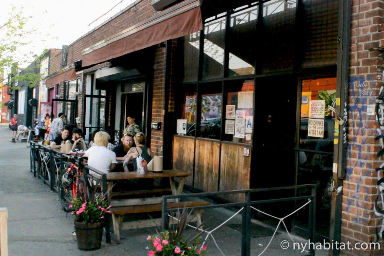 Photo de personnes assises à des tables de pique-nique sur la terrasse du bar Anchored Inn