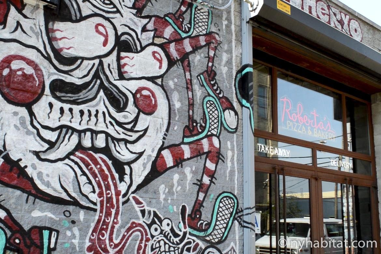 Photo d'un mur de graffiti à côté de la devanture du Roberta's Pizza