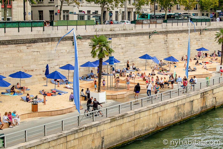 Photo de personnes se reposant le long de la Seine à Paris Plages sous des parasols bleus