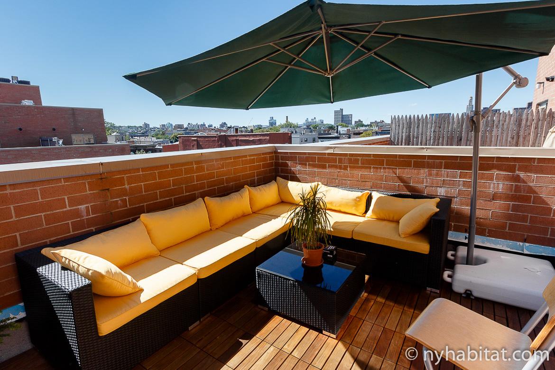 Photographie du canapé modulaire jaune et du parasol sur la terrasse de l'appartement NY 16001
